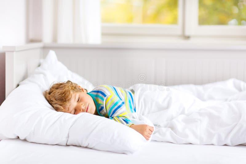 Ragazzo spensierato del bambino che dorme a letto in indumenti da letto variopinti immagini stock