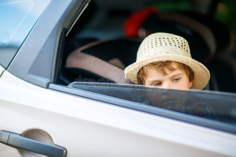 Ragazzo stanco triste del bambino che si siede in automobile durante l'ingorgo stradale fotografia stock