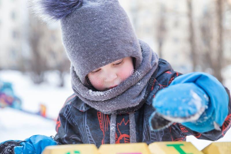 Ragazzo sul campo da giuoco nell'inverno, primo piano fotografia stock