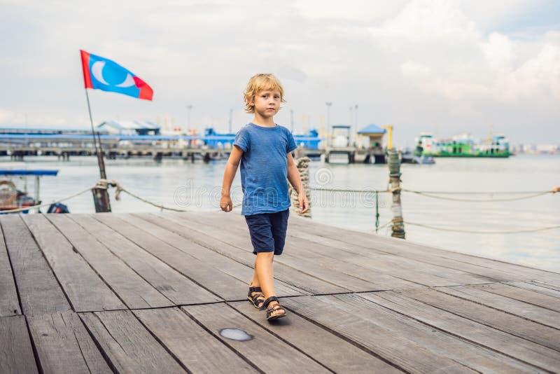 Ragazzo sul clan Tan Jetty del ponte di legno in George Town, Penang fotografia stock