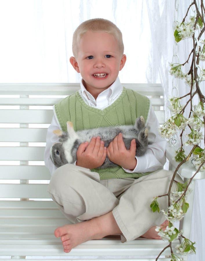 Ragazzo sul coniglietto della holding dell'oscillazione fotografie stock