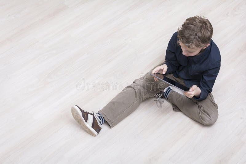 Ragazzo sul pavimento con il pc della compressa immagini stock libere da diritti