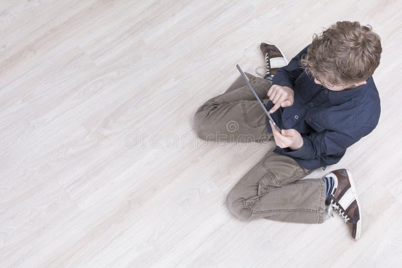Ragazzo sul pavimento con il pc della compressa immagini stock