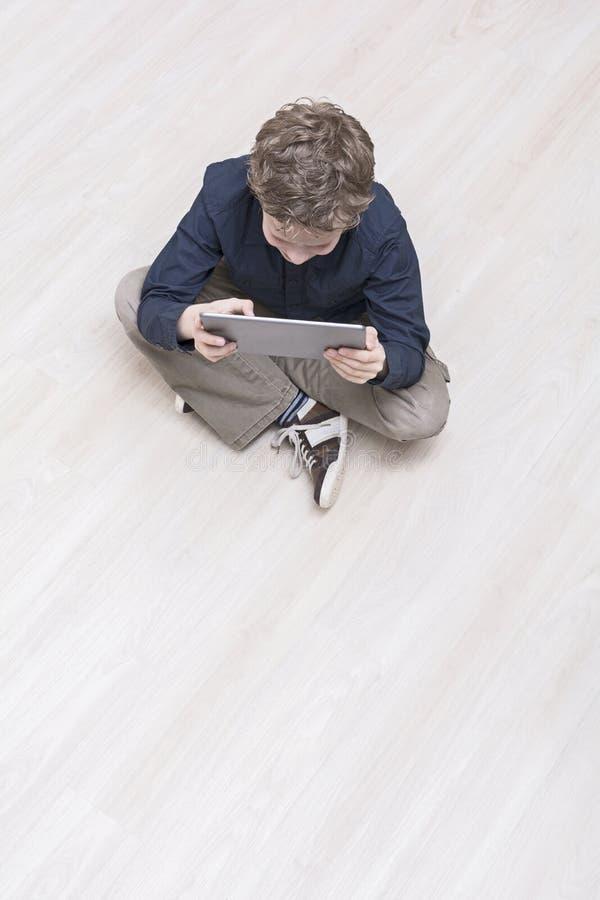 Ragazzo sul pavimento con il pc della compressa fotografie stock libere da diritti