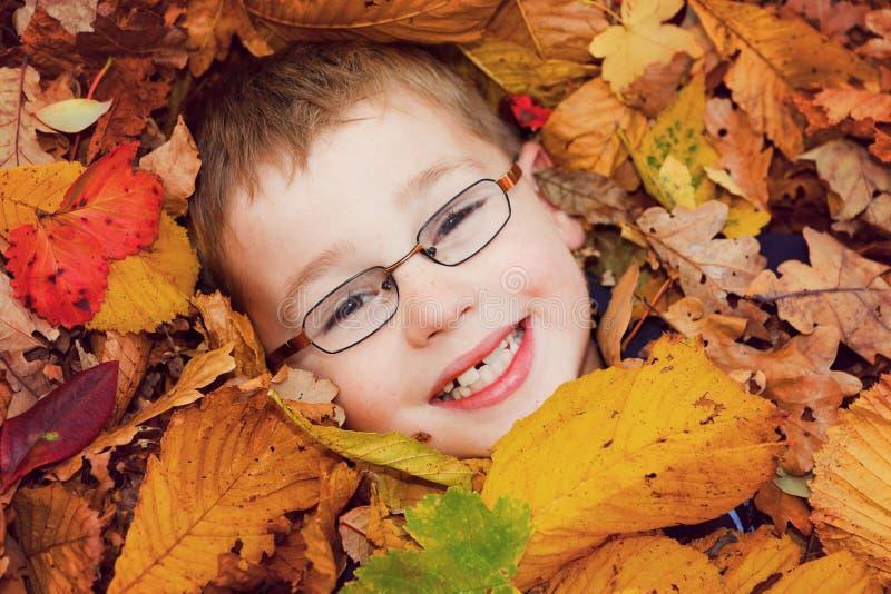 Ragazzo sul sorridere dei fogli di autunno fotografie stock libere da diritti
