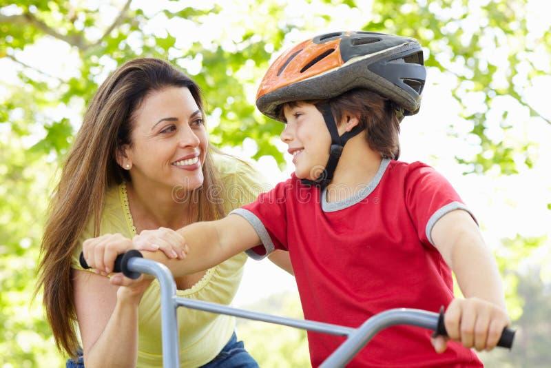Ragazzo sulla bici con la madre fotografia stock