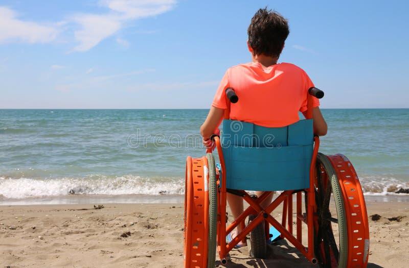 Ragazzo sulla sedia a rotelle speciale con le ruote del metallo sulla spiaggia fotografia stock
