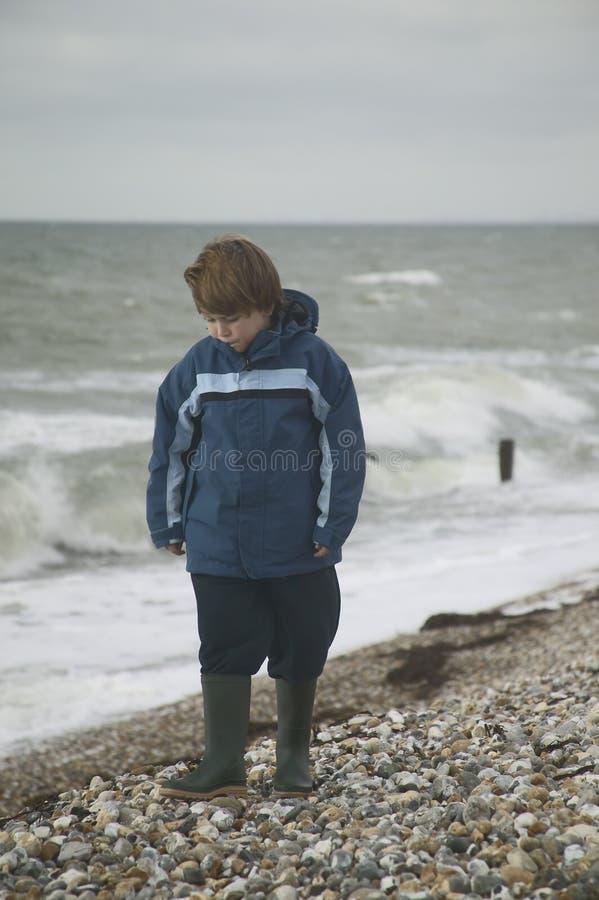 Ragazzo sulla spiaggia in inverno immagine stock libera da diritti