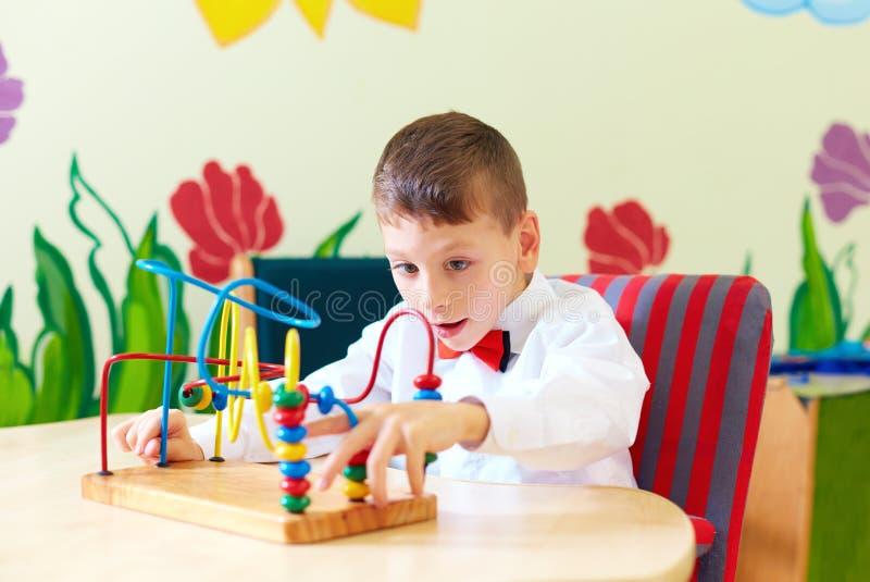 Ragazzo sveglio, bambino in sedia a rotelle che risolve puzzle logico nel centro di riabilitazione per i bambini con i bisogni sp fotografie stock