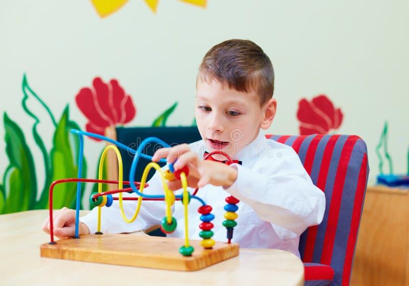 Ragazzo sveglio, bambino in sedia a rotelle che risolve puzzle logico nel centro di riabilitazione per i bambini con i bisogni sp immagini stock