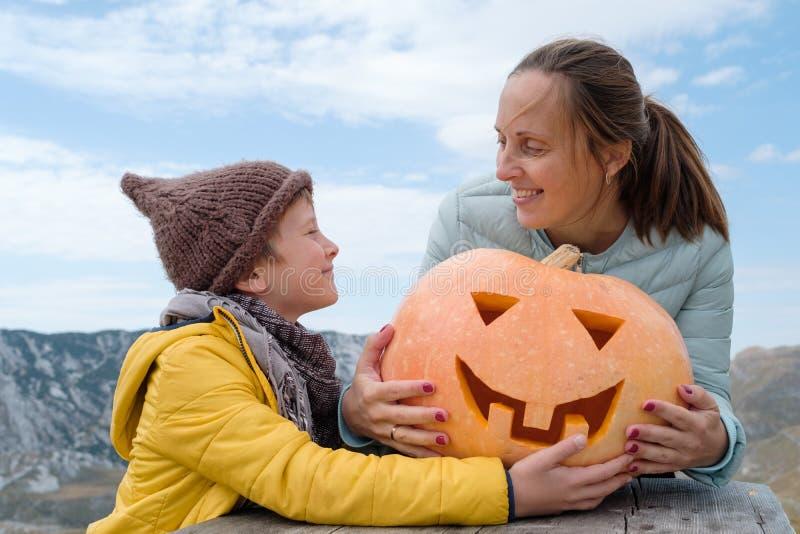 Ragazzo sveglio in cappello con la madre e la zucca scolpita Halloween sul fotografia stock