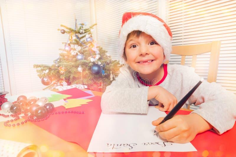 Ragazzo sveglio in cappello del ` s di Santa che scrive una lettera di Natale immagine stock libera da diritti