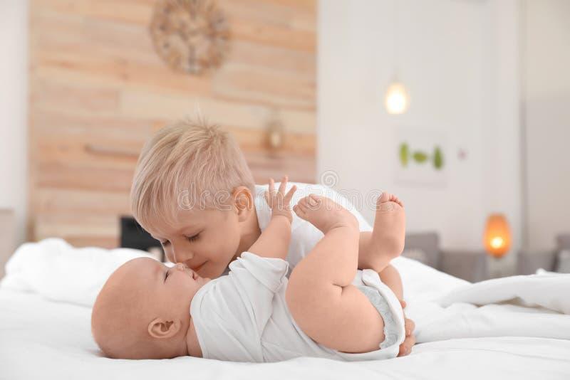 Ragazzo sveglio che bacia la sua sorellina sul letto immagine stock libera da diritti