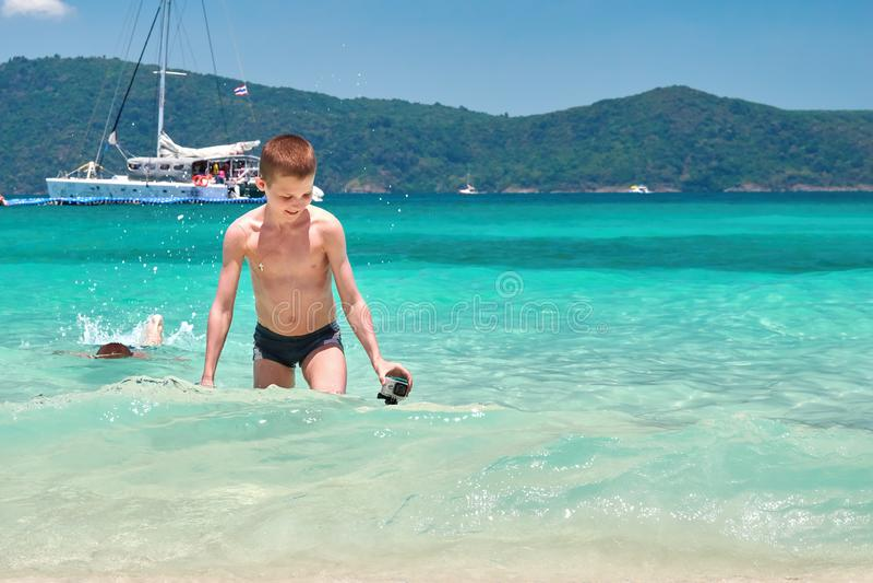 Ragazzo sveglio che esce dal mare tropicale con la macchina fotografica di azione in mani Adolescente che cammina sulla spiaggia  immagini stock libere da diritti