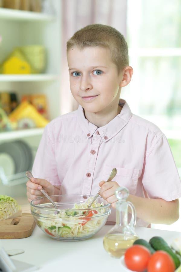 Ragazzo sveglio che fa cena sul tavolo da cucina a casa fotografia stock