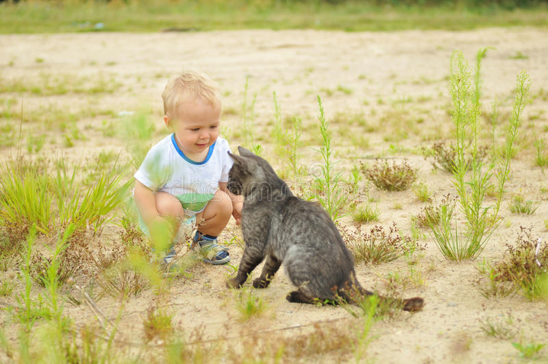Ragazzo sveglio che gioca con un gatto immagine stock