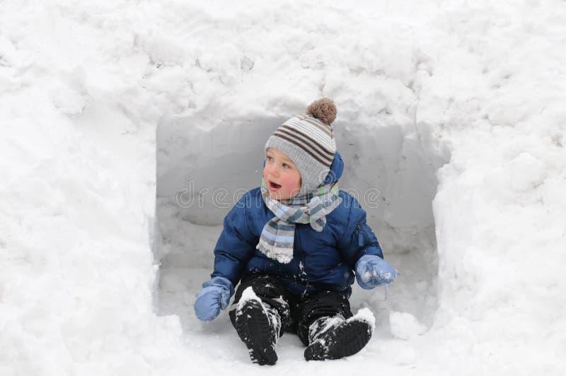 Ragazzo sveglio che gioca nella neve fotografia stock
