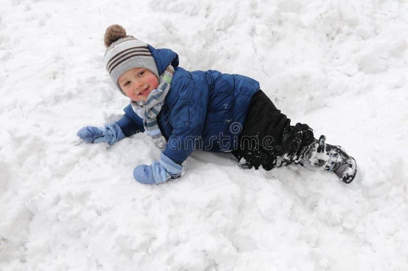 Ragazzo sveglio che gioca nella neve fotografia stock libera da diritti