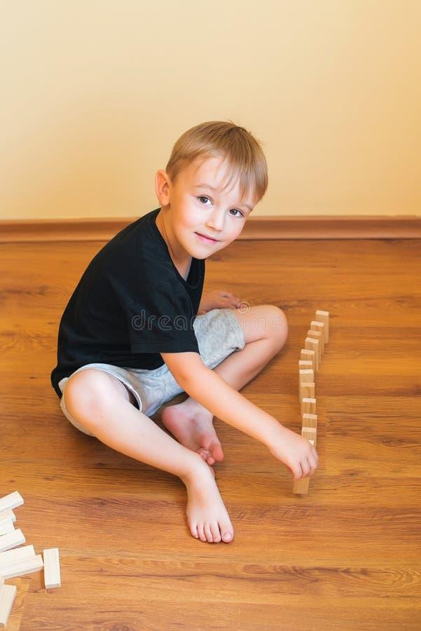 Ragazzo sveglio che gioca su un pavimento con i blocchi di legno Giocattoli di sviluppo fotografie stock libere da diritti