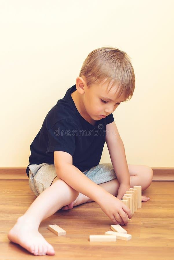 Ragazzo sveglio che gioca su un pavimento con i blocchi di legno Giocattoli di sviluppo fotografia stock libera da diritti
