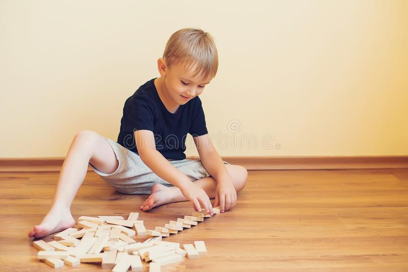 Ragazzo sveglio che gioca su un pavimento con i blocchi di legno Giocattoli di sviluppo immagine stock