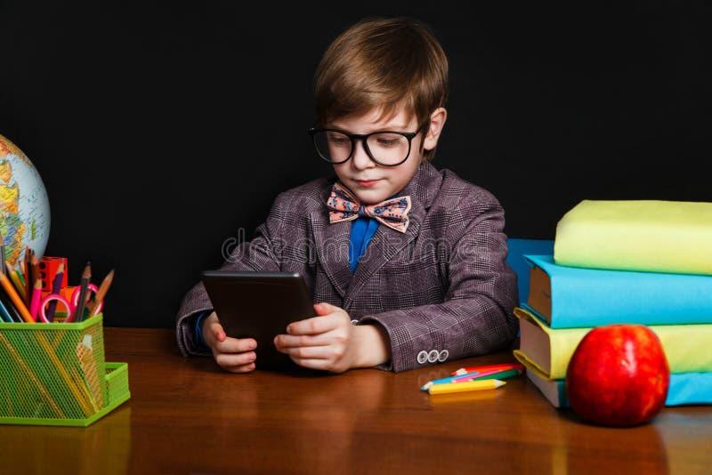 Ragazzo sveglio che legge un libro elettronico e che si siede ad uno scrittorio della scuola Di nuovo al banco fotografie stock