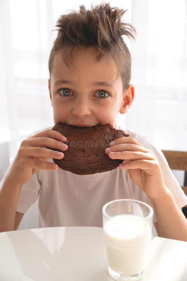 Ragazzo sveglio che si siede sulla cucina che mangia il biscotto del cioccolato con latte fotografia stock libera da diritti