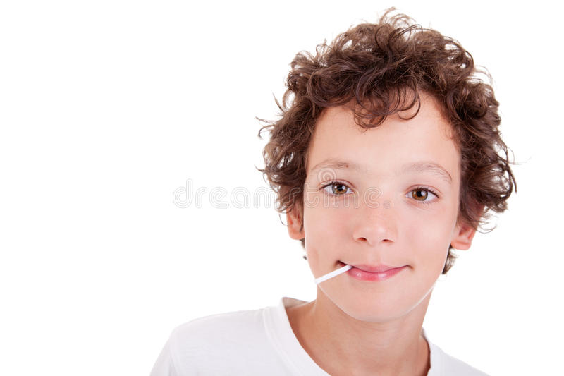 Ragazzo sveglio con una caramella sul sorridere della bocca fotografia stock