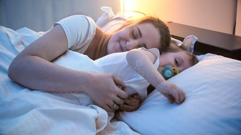 Ragazzo sveglio del bambino che dorme con la madre a letto alla notte fotografia stock libera da diritti