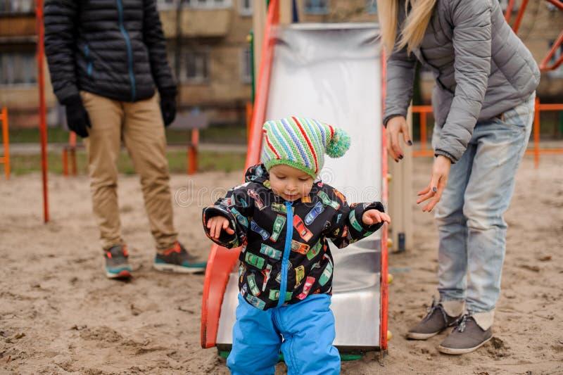 Ragazzo sveglio del bambino che gioca con i genitori sul campo da giuoco immagini stock libere da diritti