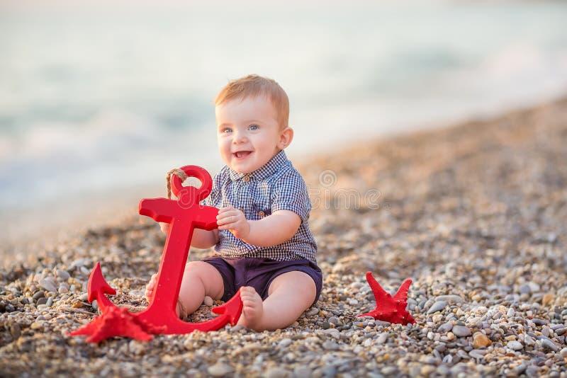 Ragazzo sveglio del bambino che gioca sulla spiaggia con la stella e l'ancora rosse del mare immagini stock libere da diritti