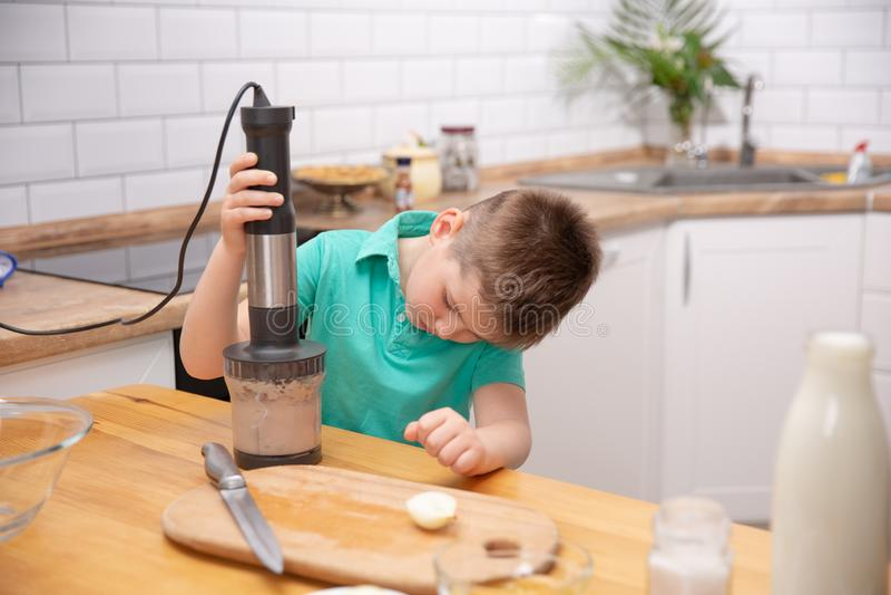 Ragazzo sveglio del bambino che per mezzo del miscelatore della mano per produrre carne tritata Preparazione del pasto nella cuci fotografia stock