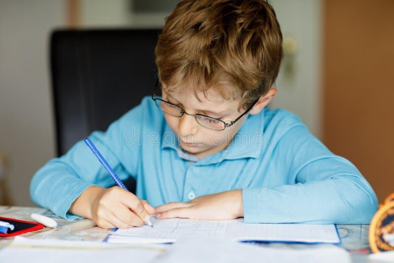 Ragazzo sveglio del bambino con i vetri a casa che fanno compito, scriventi le lettere e facenti i per la matematica con le penne fotografia stock