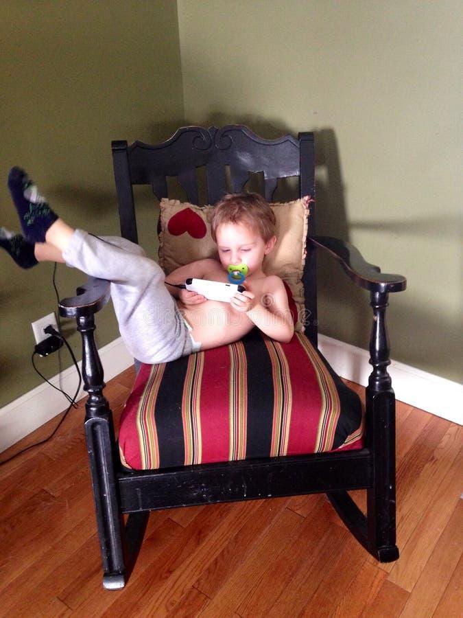 Ragazzo sveglio del bambino con una tettarella e un telefono cellulare fotografia stock libera da diritti
