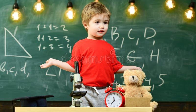 Ragazzo sveglio della scuola elementare con il microscopio al suo scrittorio a casa Giovane scienziato che fa gli esperimenti nel fotografia stock