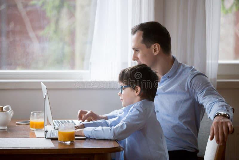 Ragazzo sveglio e papà che lavorano insieme ai computer portatili in cucina fotografia stock