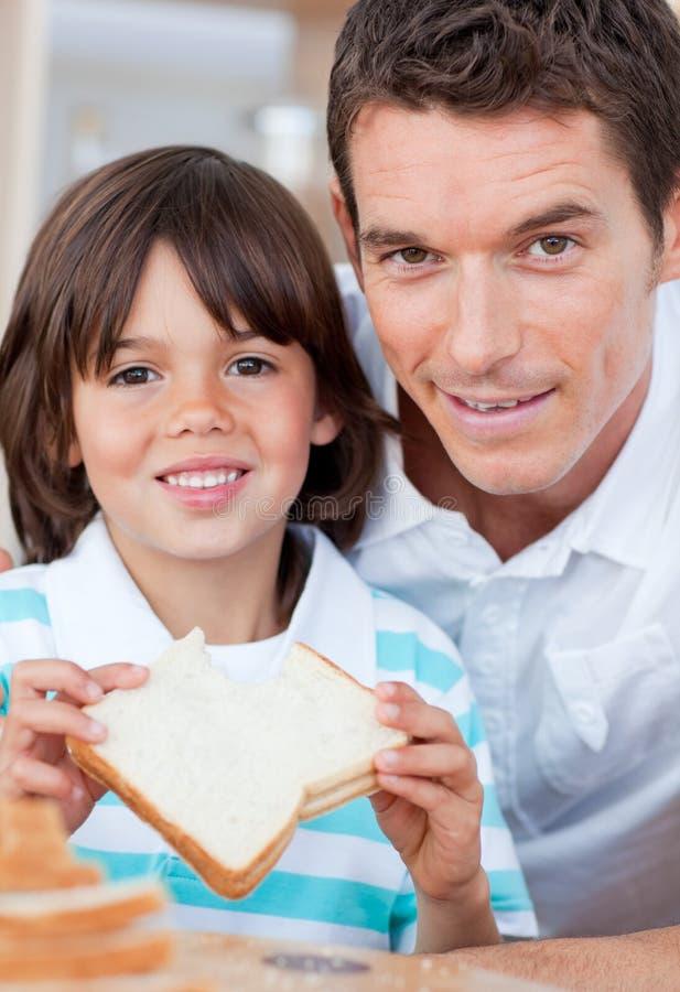 Ragazzo sveglio e suo il padre che mangiano pane fotografia stock