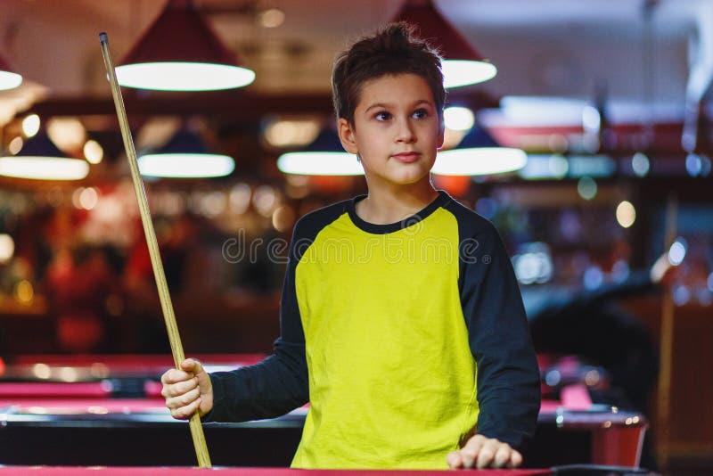 Ragazzo sveglio nel biliardo giallo dei giochi della maglietta o stagno in club Il ragazzino impara giocare lo snooker Ragazzo co fotografia stock libera da diritti