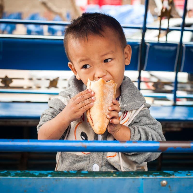 Ragazzo sveglio non identificato che gode del panino laos fotografia stock libera da diritti