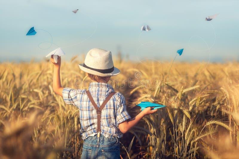 Ragazzo sveglio in un cappello che getta un aeroplano di carta Bambino in un giacimento di grano immagini stock libere da diritti