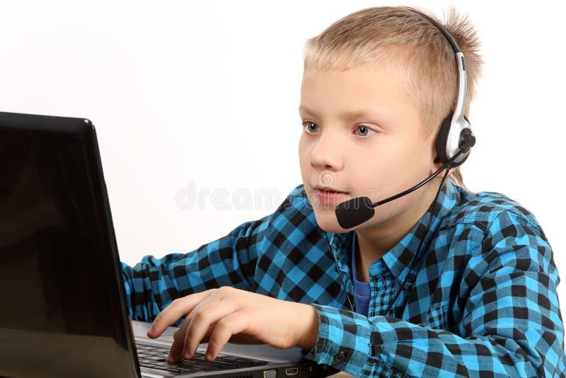 Ragazzo teenager bello con il computer portatile immagine stock