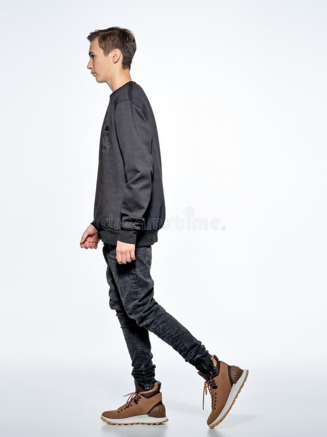 Ragazzo teenager che posa allo studio Camminata vicino immagini stock libere da diritti