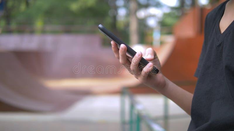 Ragazzo teenager da solo facendo uso di un telefono cellulare contro lo sfondo di un parco del pattino mentre altri bambini attiv fotografia stock