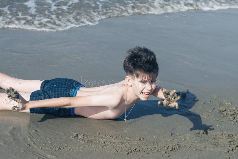 Ragazzo teenager divertente divertendosi sul ¾ n della sabbia Ð la spiaggia e gli spaventi con la sua mano fotografia stock libera da diritti