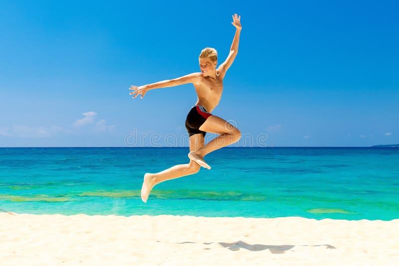 Ragazzo teenager felice divertendosi sulla spiaggia tropicale Vacanza di estate fotografie stock libere da diritti