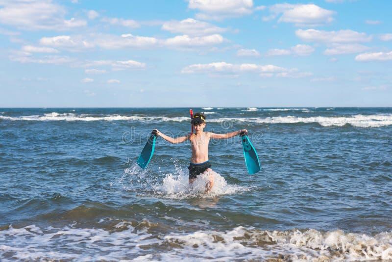 Ragazzo teenager felice nelle alette di nuotata e nella maschera immergersi che esegue il ¾ n di Ð l'onda del mare durante le vac fotografia stock libera da diritti
