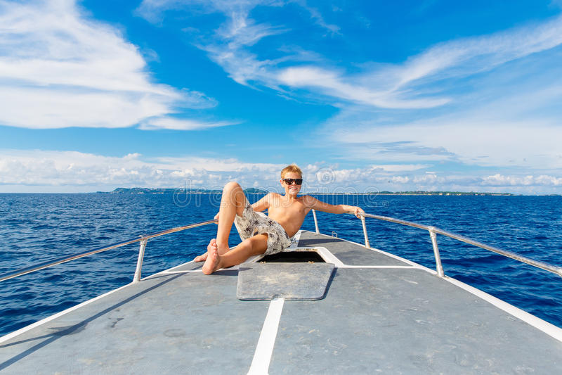 Ragazzo teenager felice in occhiali da sole sull'yacht Mare tropicale nella b immagine stock libera da diritti