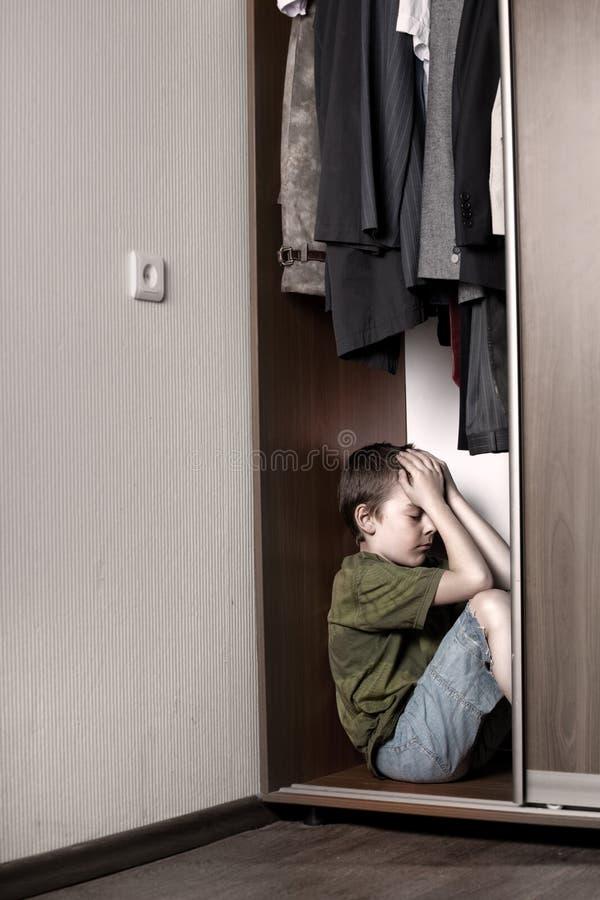 Ragazzo triste, nascondentesi nell'armadio immagine stock