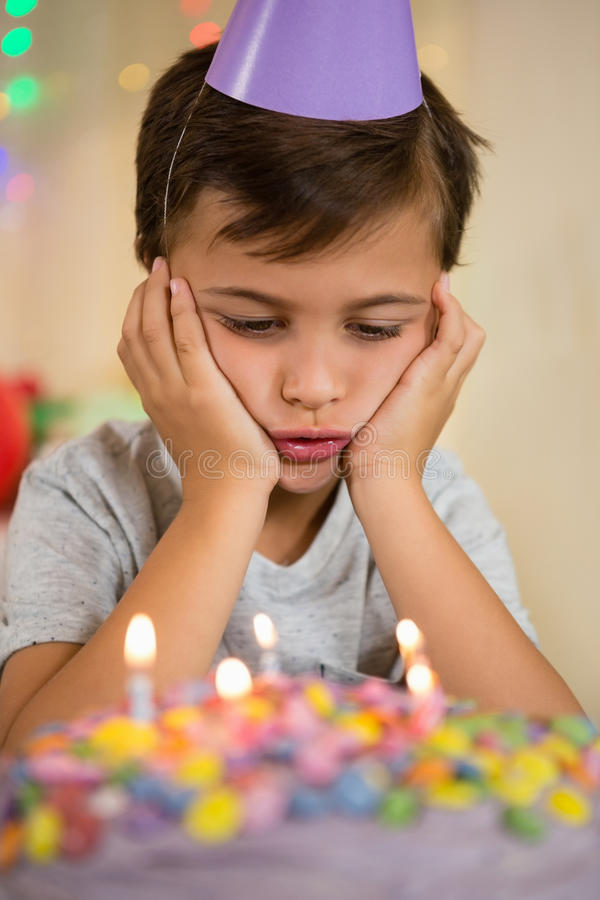Ragazzo turbato che si siede con la torta di compleanno immagine stock