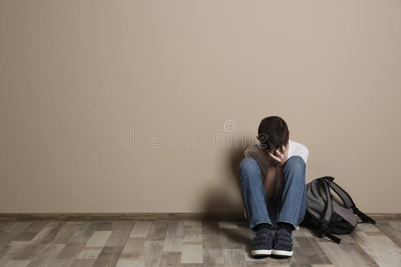Ragazzo turbato con lo zaino che si siede sul pavimento alla parete di colore spazio immagini stock